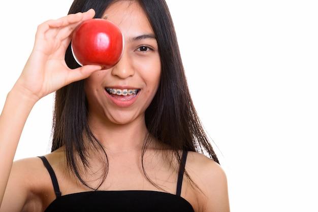 Junge glückliche asiatische teenager-mädchen lächelnd, während auge mit rotem apfel bedeckt