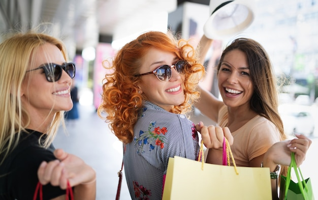Junge glückliche attraktive mädchen mit einkaufstüten in der stadt.