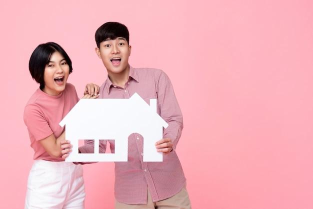 Junge glückliche aufgeregte asiatische paare, die papierhaus halten