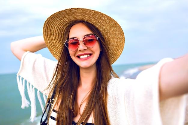 Junge glückliche blonde mädchen machen selfie, tragen strohhut und herz niedliche sonnenbrille, genießen sie ihre sommerferien in der nähe von ozean.