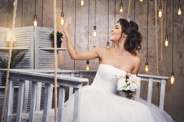 Junge glückliche braut, die schönes üppiges kleid im raum mit vielen glühbirnen trägt