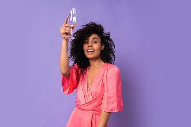 Junge glückliche brazillianische frau mit lockigem haar im rosa stilvollen kleid, das mit glas champagner über lila wand aufwirft. partystimmung.