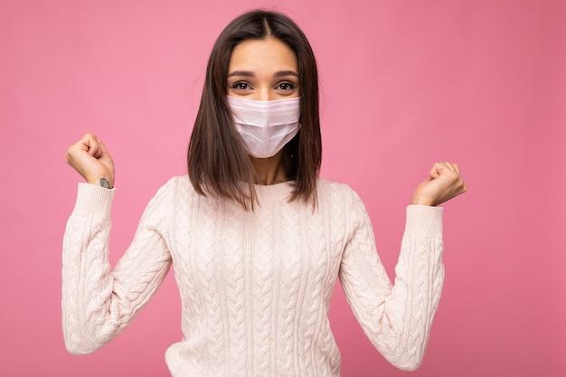 Junge glückliche brünette frau, die eine anti-virus-schutzmaske trägt, um andere vor corona covid zu schützen