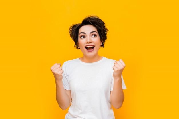 Junge glückliche brünette frau mit einem kurzen haarschnitt in einem weißen t-shirt auf gelbem hintergrund. porträt einer jungen frau mit verschiedenen emotionen auf gelbem grund. platz für text