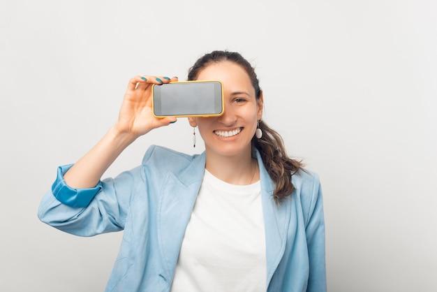 Junge glückliche dame bedeckt einen teil ihres gesichts mit ihrem telefonbildschirm.