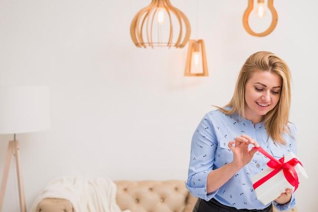 Junge glückliche dame mit geschenkbox nahe sofa im raum
