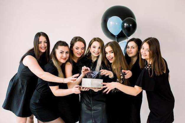 Junge glückliche damen in den schwarzen kleidern, die geburtstag im studio feiern. beste freundinnen, die spaß haben, geburtstagstorte zu halten und zu lächeln. geburtstagsfeier, feiertag, frauentagskonzept