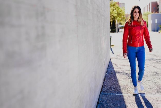 Junge glückliche eben emanzipierte frau nahe bei einer betonmauer, gekleidet in der bunten kleidung und suchte nach ihrem ersten job.