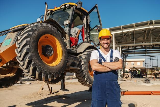 Junge glückliche engagierte kaukasische raffineriearbeiterin in schützender arbeitskleidung, die neben bulldozer mit verschränkten armen steht.