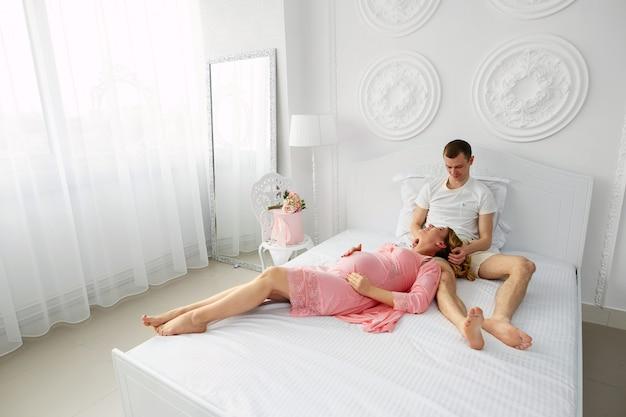 Junge glückliche familie, die auf das baby wartet. mann umarmt sanft schwangere frau im schlafzimmer. lächelnde schwangere paare im schlafzimmer. 9 monate der schwangerschaft