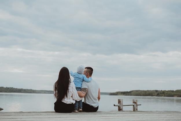 Junge glückliche familie, die auf dem pier im sommer am wasser sitzt
