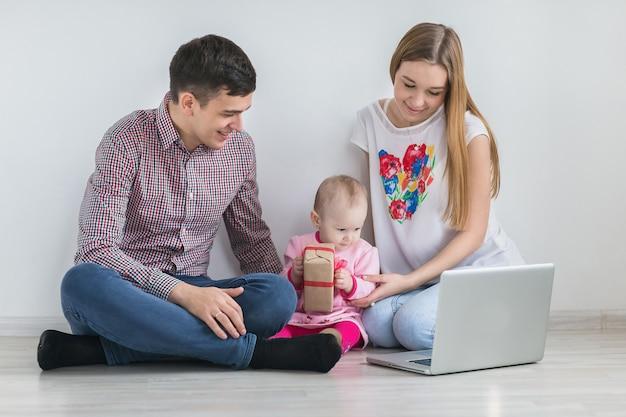Junge glückliche familie, die auf einem laptop läuft