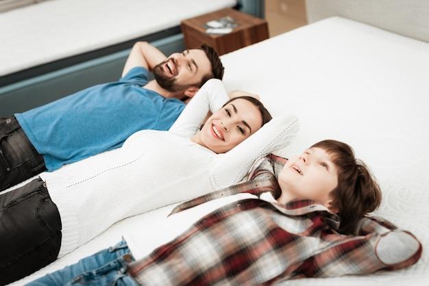 Junge glückliche familie, die auf matratze im speicher liegt