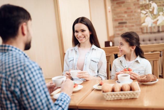 Junge glückliche familie, die kuchen in der cafeteria isst.