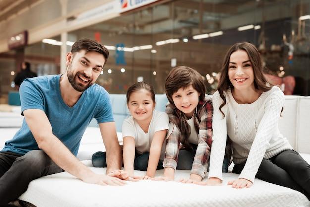 Junge glückliche familie, die zusammen matratze wählt