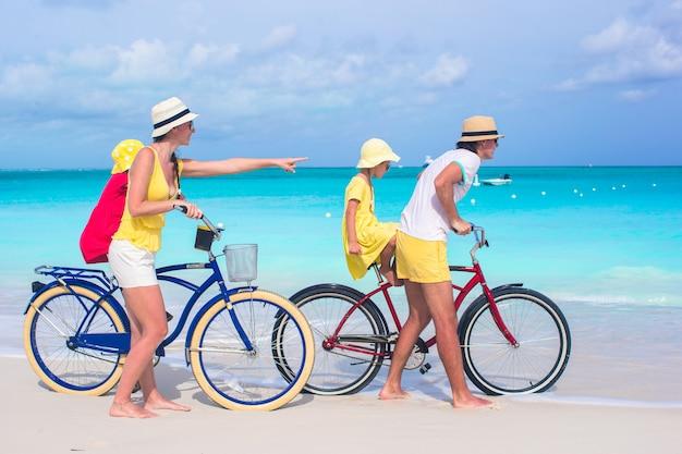 Junge glückliche familie fahrradfahren am tropischen strand