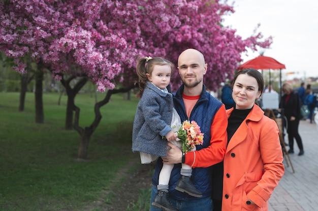 Junge glückliche familie im park im frühjahr