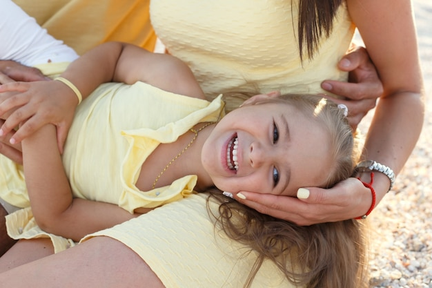 Junge glückliche familie in gelber kleidung spielt mit ihrem kind am meer