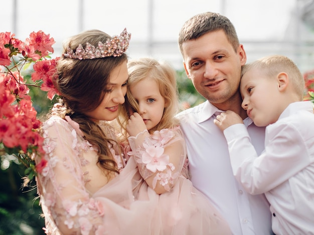 Junge glückliche familie - mama, papa, tochter und sohn, in einem blühenden frühlingsgarten