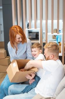 Junge glückliche familie mit dem kind, welches die kästen zusammen sitzen auf sofa auspackt