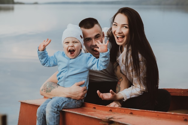 Junge glückliche familie mit ihrem sohn sitzen und lächeln in einem boot am wasser im sommer