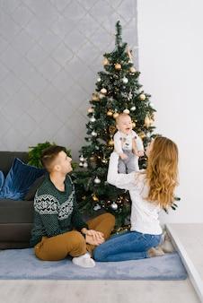 Junge glückliche familie sitzt auf dem boden nahe dem weihnachtsbaum