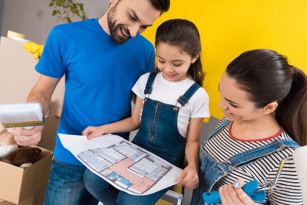 Junge glückliche familie studiert plan von räumen im haus.