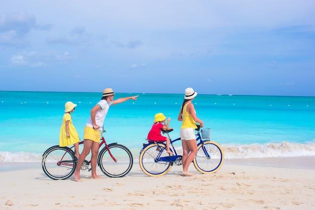 Junge glückliche familienreitfahrräder, die strandferien duting sind