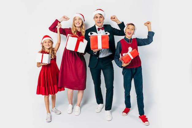 Junge glückliche familienweihnachten mit den kindern in den weihnachtsmützen