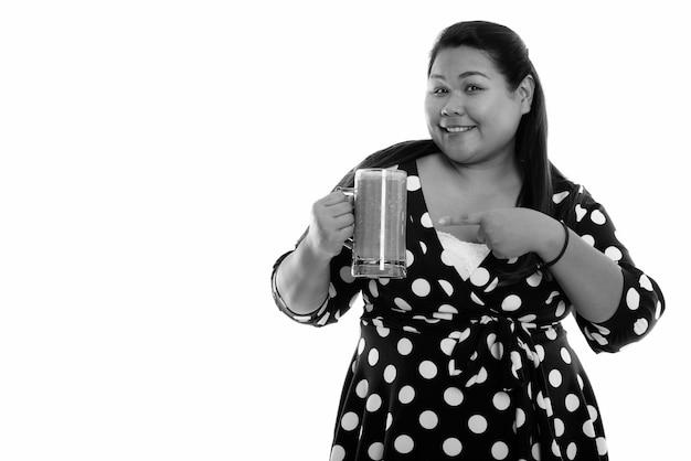 Junge glückliche fette asiatische frau, die lächelt, während sie hält und auf glas gemüsesmoothie zeigt