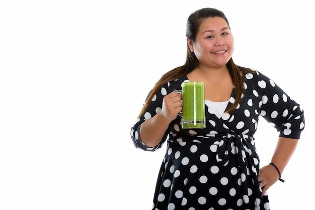 Junge glückliche fette asiatische frau, die mit kleid lächelt