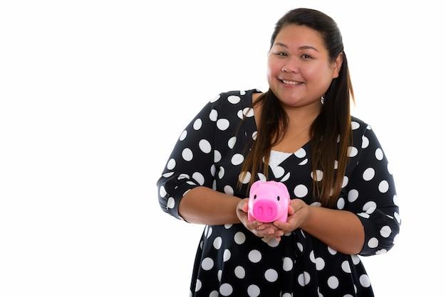 Junge glückliche fette asiatische frau lächelnd, während sie ein sparschwein hält