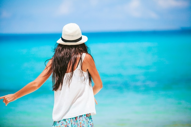Junge glückliche frau am weißen strand, der geht. junge schöne frau an tropischer küste.