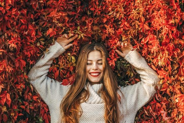 Junge glückliche frau auf einer wand aus roten efeublättern. sie lächelt.