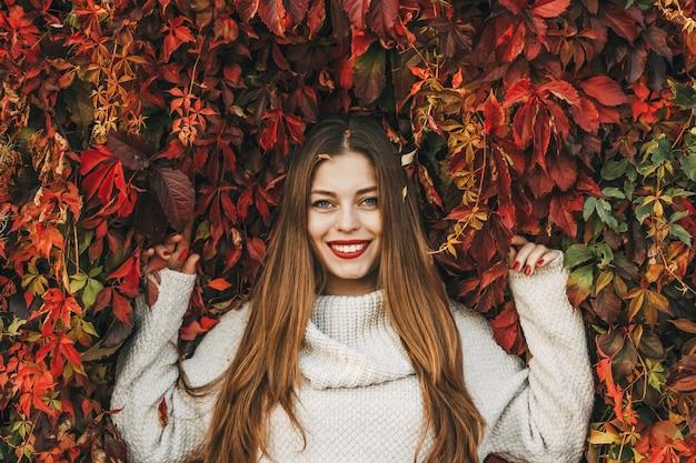Junge glückliche frau auf einer wand aus roten efeublättern.