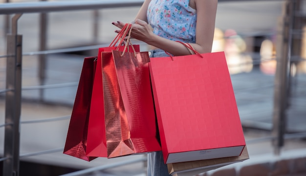 Junge glückliche frau des lebensstils, die einkaufstasche mit dem genießen am einkaufszentrum hält.