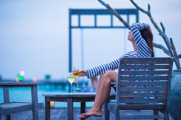 Junge glückliche frau, die am abend auf sommerferien sich entspannt