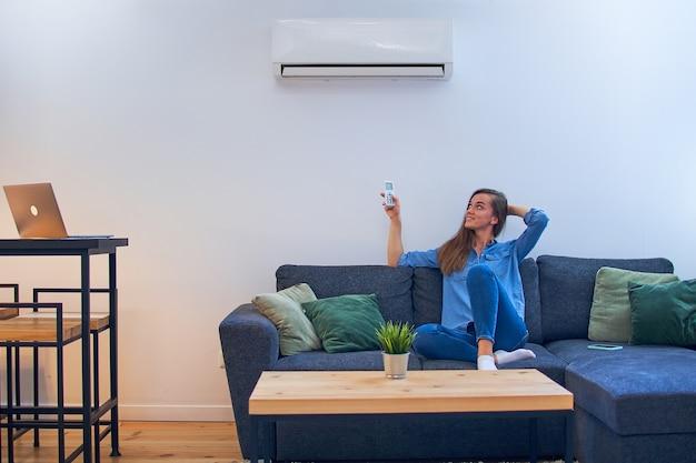 Junge glückliche frau, die auf couch unter klimaanlage sitzt und komforttemperatur mit fernbedienung am modernen haus einstellt