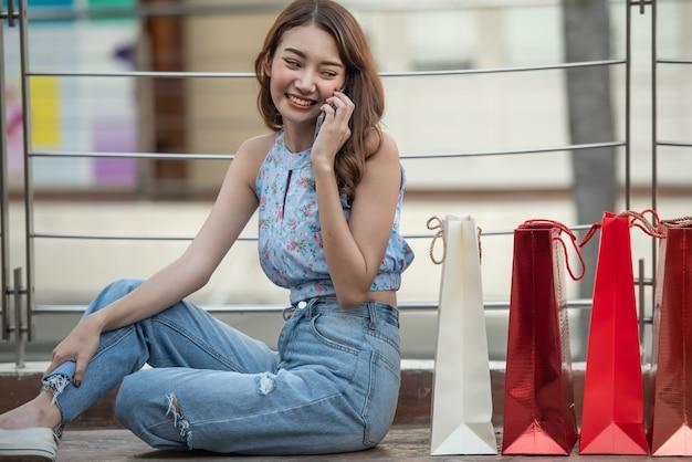 Junge glückliche frau, die auf dem boden mit einkaufstaschen sitzt und im einkaufszentrum auf smartphone spricht.