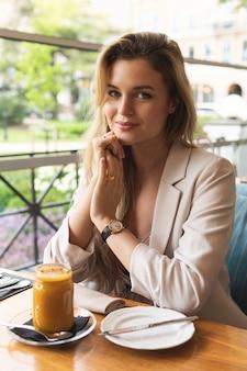 Junge glückliche frau, die auf der terrasse des restaurants sitzt
