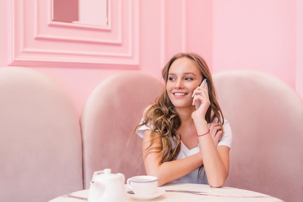 Junge glückliche frau, die auf handy mit freund spricht, während sie allein in der innenausstattung des modernen coffeeshops sitzt, lächelndes hipster-mädchen, das mit handy telefoniert, während sie nach dem gehen im sommertag entspannt