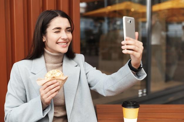 Junge glückliche frau, die ein selfie mit einem donut an einem kaffeegeschäft nimmt, zwinkert und am smartphone lächelt.