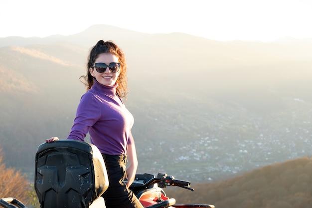 Junge glückliche frau, die extreme fahrt auf atv quad-motorrad in den herbstbergen bei sonnenuntergang genießt.