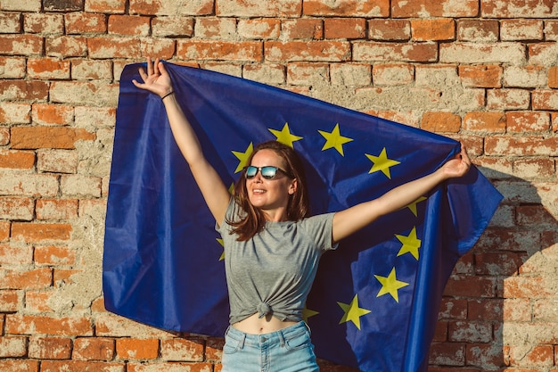 Junge glückliche frau, die flagge der europäischen union hält, förderung der eu