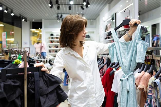 Junge glückliche frau, die hellblaues kleid im bekleidungsgeschäft hält