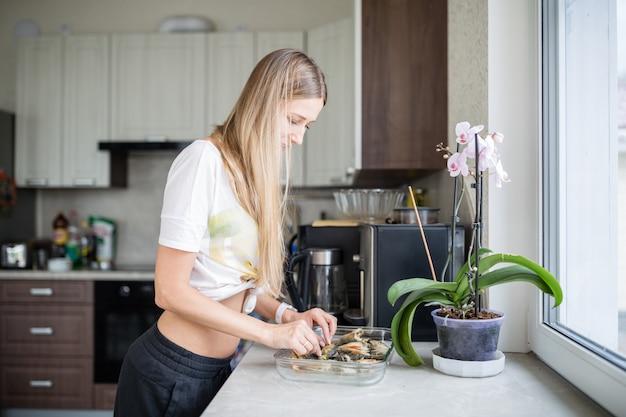 Junge glückliche frau, die in der küche kocht