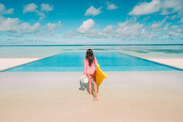 Junge glückliche frau, die in einem swimmingpool sich entspannt