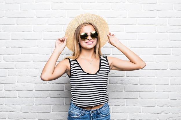 Junge glückliche frau, die in sonnenbrille und sommerhut über weiße backsteinmauer lächelt