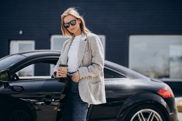 Junge glückliche frau, die kaffee durch das auto trinkt