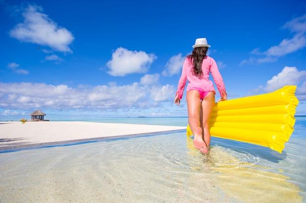 Junge glückliche frau, die mit luftmatratze im swimmingpool sich entspannt
